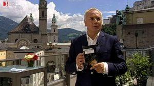 """3sat-Kulturzeit-Moderator Ernst A. Grandits präsentiert Baumanns Krimi """"Zauberflötenrache"""" während einer Kulturzeit-Extraausgabe zu den Salzburger Festspielen."""